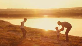Young family frolicked together to play football football on the beach at sunset. With two boys working with his father stock video