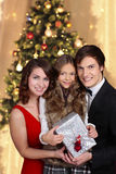 Young family in front of christmas tree Stock Photography