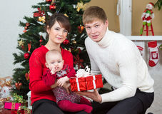Young family in front of Christmas tree Royalty Free Stock Image