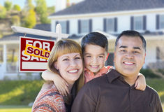 Young Family in Front of Sold Real Estate Sign and House Royalty Free Stock Photos