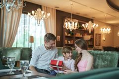 Young family with a gift. In a restaurant Royalty Free Stock Image