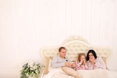 Young family got sick or ill sneezing in bed at home. RChild Mom and Dad got sick cold ill, with temperature of virus. Young couple enjoys napkins. Woman with Stock Photography