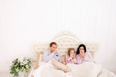 Young family got sick or ill sneezing in bed at home. RChild Mom and Dad got sick cold ill, with temperature of virus. Young couple enjoys napkins. Woman with Royalty Free Stock Image