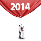 Young family grabbing new future banner. Portrait of happy family grabbing new future in 2014 - isolated on white Royalty Free Stock Photos