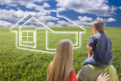 Young Family in Grass Field with Ghosted House in Front Royalty Free Stock Images