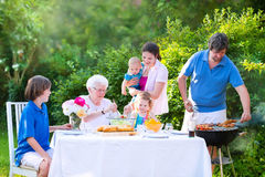 Young family grilling meat for lunch with grandmother Stock Photo