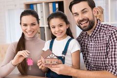 Young family is happy to buy new house, holding keys from house and miniature house. stock photos