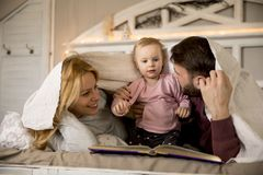 Young family having fun on the bed. In the room Stock Photo