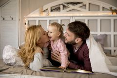 Young family having fun on the bed. In the room Royalty Free Stock Photos