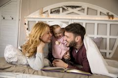 Young family having fun on the bed. In the room Stock Photography