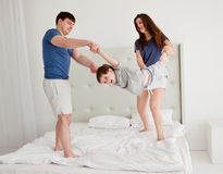 Young Family Having Fun Bouncing On Bed Stock Photos