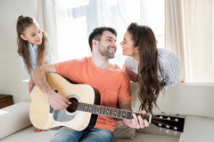 Young family having fun with guitar at home. Happy young family having fun with guitar at home stock images