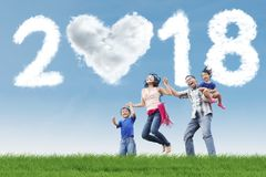 Young family having fun in the meadow. Picture of young family having fun in the meadow with clouds shaped heart and numbers 2018 royalty free stock photos
