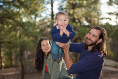 Young family having fun in nature. Shallow DOF, baby's face in focus Stock Photo