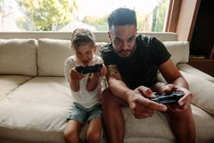 Young family having fun playing video games at home. Father and son with video game controllers sitting on sofa. Young family having fun playing video games at Royalty Free Stock Image
