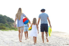 Young family having fun running on beach at sunset. Royalty Free Stock Photos