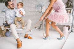 Young family having fun with sled in white studio Royalty Free Stock Images