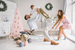 Young family having fun with sled in white studio Stock Photo