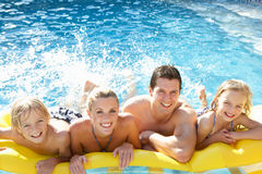 Young family having fun together in pool stock images