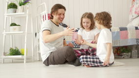 Young family having fun weekend. Father playing with two children. Young father playing with children, sitting on the floor in the bedroom. They have fun stock footage