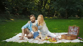 Young family having picnic outdoors stock video