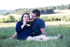 Young family having picnic outdoors. Young family men and pregnant women having picnic outdoors Stock Photo