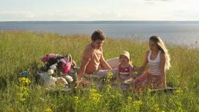 Young family having picnic by the river stock footage