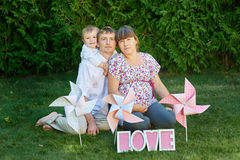 Young family having a picnic with windmills on the grass Stock Images