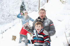 Young Family Having Snowball Fight. In Snowy Landscape royalty free stock images