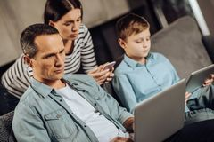 Young family having their attention on their gadgets. Addicted to gadgets. Pleasant young family sitting on the couch and having their attention solely on their Royalty Free Stock Images