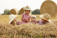 Young family on haystacks in cowboy hats Stock Photo