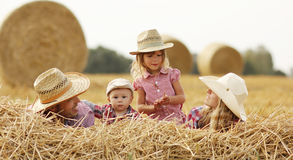 Young family on haystacks in cowboy hats Stock Image