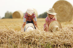 Young family on haystacks in cowboy hats Royalty Free Stock Image