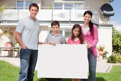 Young family holding a black white board Stock Image