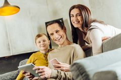 Young family holding gadgets and smiling. We love gadgets. Pleasant upbeat young family sitting on the couch and smiling at the camera brightly while posing with Stock Photos