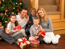 Young family at home exchanging gifts. Smiling at camera royalty free stock photography
