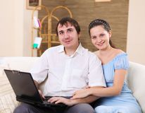 Young family at home with a laptop Royalty Free Stock Photos