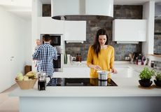 A young family at home, a man holding a baby and a woman cooking. A portrait of young family standing in a kitchen at home, a men holding a baby and a women royalty free stock photography