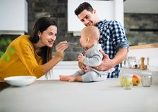 A young family at home, a man holding a baby and a woman feeding her. A portrait of young family standing in a kitchen at home, a men holding a baby and a women royalty free stock photo