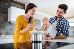 A young family at home, a man holding a baby and a woman feeding her. A portrait of young family standing in a kitchen at home, a men holding a baby and a women stock image