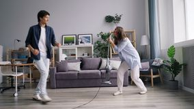 Young family dancing singing during housework using vacuum cleaner at home