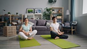 Young family husband and wife doing yoga then relaxing in lotus position. Young family husband and wife are doing yoga then relaxing in lotus position sitting on stock footage