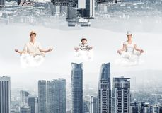 Young family keeping mind conscious. Young family keeping eyes closed and looking concentrated while meditating on clouds in the air between two urban worlds Royalty Free Stock Images