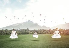 Young family keeping mind conscious. Young family keeping eyes closed and looking concentrated while meditating on clouds in the air with bright and beautiful Royalty Free Stock Images