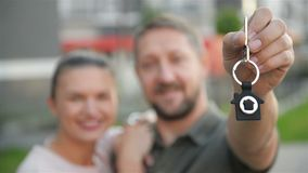 Young Family With The Keys On The Background Of Their New Home. Good Mood, Together.