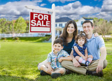 Young Family With Kids In Front of Custom Home and For Sale Sign. Young Family With Children In Front of Custom Home and For Sale Real Estate Sign Stock Photo