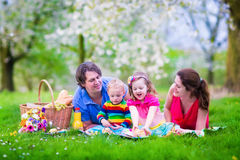 Young family with kids having picnic outdoors. Parents with two children relax in a blooming summer garden. Mother, father, little girl and baby boy eat Royalty Free Stock Photography