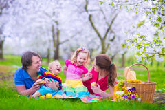 Young family with kids having picnic outdoors. Parents with two children relax in a blooming summer garden. Mother, father, little girl and baby boy eat Stock Photo