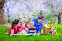 Young family with kids having picnic outdoors. Parents with two children relax in a blooming summer garden. Mother, father, little girl and baby boy eat Royalty Free Stock Photos