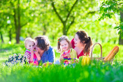 Young family with kids having picnic outdoors. Parents with two children relax in a sunny summer garden. Mother, father, little girl and baby boy eat sandwich Royalty Free Stock Photos
